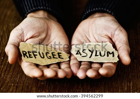 closeup of the hands of a young man with two pieces of paper with the words refugee and asylum written in each one, with a dramatic effect