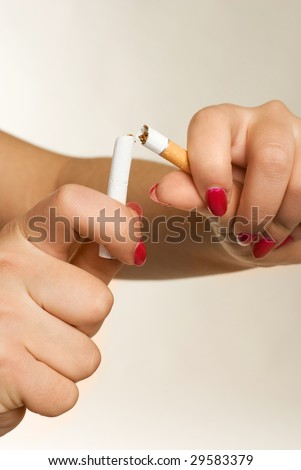 closeup of the hands of a young woman breaking a cigarette