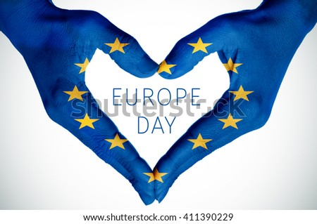 closeup of the hands of a young woman forming a heart patterned as the flag of the European Union and the text Europe Day #411390229