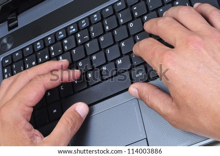 closeup of the hands of someone who is working with a laptop