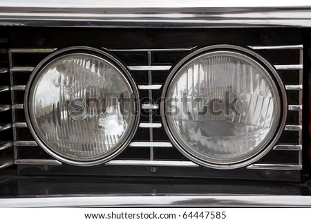 Closeup of the headlights of a car - stock photo