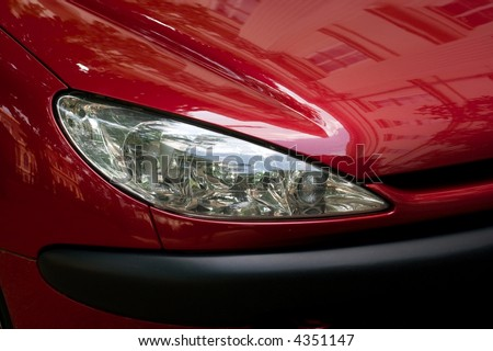 Closeup of the headlights of a red car - stock photo