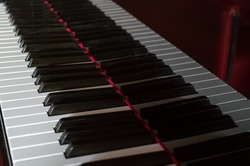 Closeup of the keyboard of a piano. Keys reflecting in the body of the piano