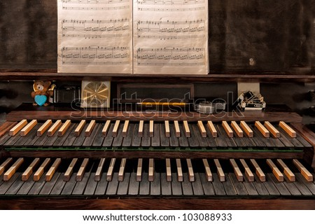 Closeup of the keys and sheet music on a pipe organ in a Christian church