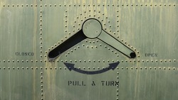 Closeup of the latch on the door of a military plane with rivets on weathered fuselage