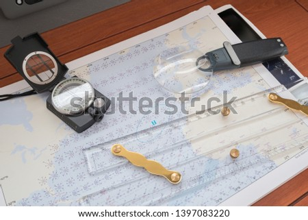 Closeup of the navigation station of a sailing vessel with navigation chart, magnifying lens, parallel ruler and a handheld compass #1397083220