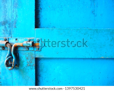Closeup of the old and classic rusty door latch and lock on wooden bright blue painted door. Vintage decoration closed wooden door and lifestyle concept