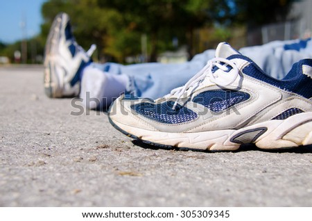 Closeup of the shoe from a pedestrian that is a victim of automobile hit and run on a roadside with the victim laying in the background.