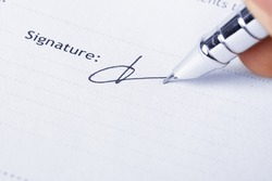 closeup of the signature and pen on a document paper