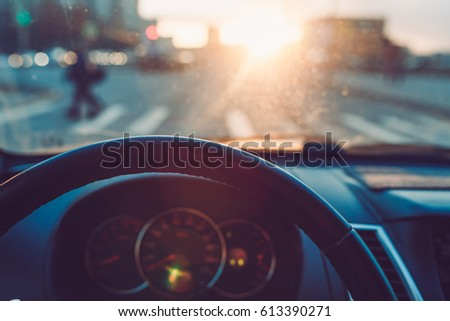 Closeup of the steering wheel in the car on the background of wonderful sunset. View of the road, pedestrian crossing. The view through car windscreen.  Warm toned picture, vintage tone.