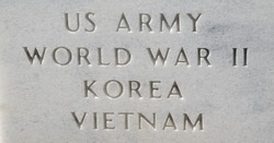 Closeup of the tombstone of a US Army veteran who served in three wars