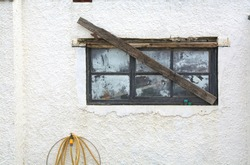 Closeup of the white wall of a house  with an old barricaded window with dirty panes and a yellow water hose dangling from a tap.