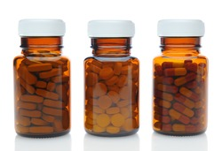 Closeup of three brown medicine bottles filled with different pills and medications with their caps on over a white background with reflection. Horizontal format.