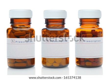 Closeup of three brown medicine bottles filled with different pills and medications with their caps on over a white background with reflection.