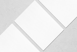 Closeup of three empty white rectangle poster mockups lying diagonally with soft shadow on neutral light grey concrete background. Flat lay, top view. Open composition.