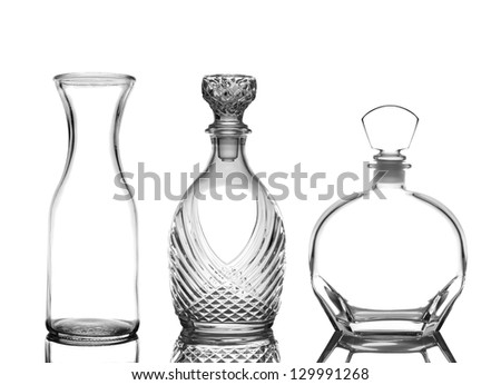 Closeup of three glass decanters on white with reflections. Wine Carafe and cognac decanters are depicted.