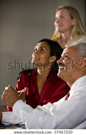 Closeup of three happy multiethnic businesspeople watching together - stock photo