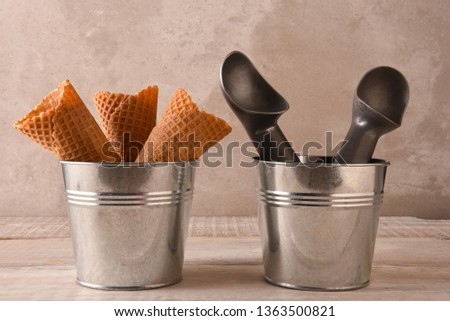 Closeup of three ice cream cones in a small metal bucket next to a pail with two scoops.