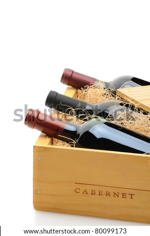 Closeup of three red wine bottles in a wooden shipping crate. The crate is partially open with excelsior packing. Vertical format over a white background with reflection. - stock photo