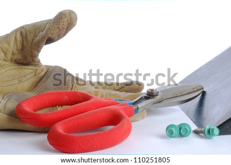 Closeup of tin snips, work gloves; piece of sheet metal and screws against neutral background. - stock photo
