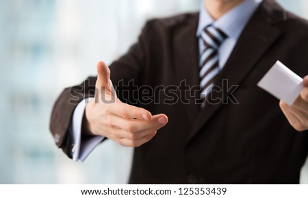 Closeup of torso of confident business man wearing elegant suit sharing his blank business card
