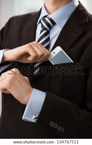 Closeup of torso of confident business man wearing elegant suit taking mobile phone from pocket