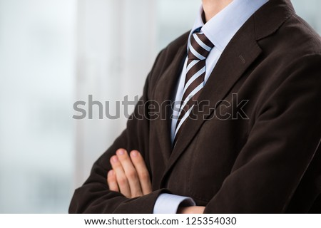 Closeup of torso of confident business man wearing elegant suit with hands folded
