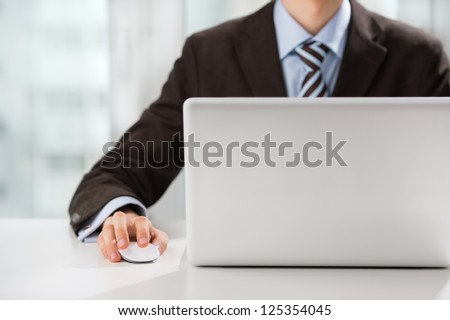 Closeup of torso of confident business man wearing elegant suit working with his laptop at office