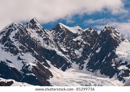 Closeup of towering sharp mountain peaks with glacier ice caps.