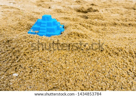 Closeup of toy pyramid on the beach. Blue plaything lies on the sand. Shallow depth of field, soft focus, selective focus. #1434853784
