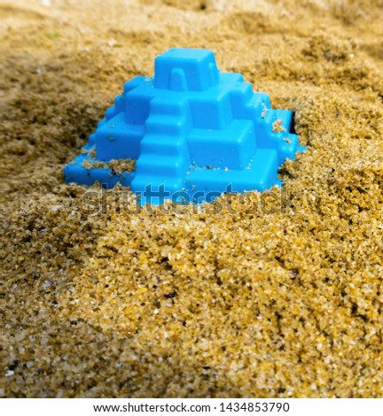 Closeup of toy pyramid on the beach. Blue plaything lies on the sand. Shallow depth of field, soft focus, selective focus. #1434853790