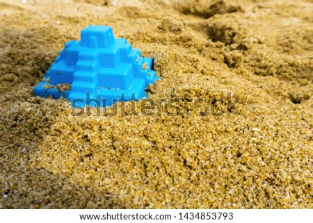 Closeup of toy pyramid on the beach. Blue plaything lies on the sand. Shallow depth of field, soft focus, selective focus. #1434853793