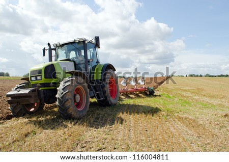 Closeup of tractor plowing agricultural field in autumn.