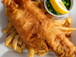 closeup of traditional British pub fare, a crispy battered haddock filet with french fried chips and green peas