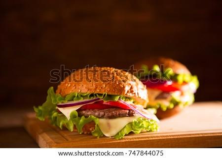 closeup of traditional cheeseburger or hamburger and french fries.