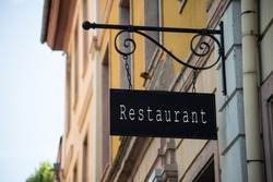closeup of traditional signboard of french restaurant on vintage signboard in the street