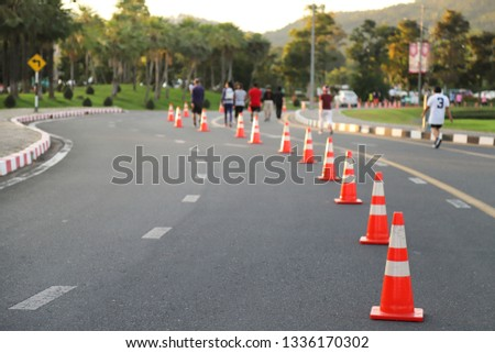 Closeup of traffic poles, traffic lane, jogging trcak on the street and joggers with natural background in the evening of sunny day. The good public  service for people by the idea of safety first. #1336170302