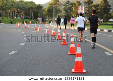 Closeup of traffic poles, traffic lane, jogging trcak on the street and joggers with natural background in the evening of sunny day. The good public  service for people by the idea of safety first. #1336171121