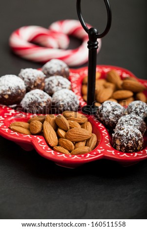 Closeup of tray of almonds and chocolate balls with hard handy heart with red swirls in background