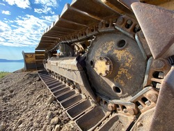Closeup of treads on a bulldozer on a dirt road with blue sky