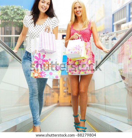 Closeup of two attractive happy girls out shopping. They are moving on escalator