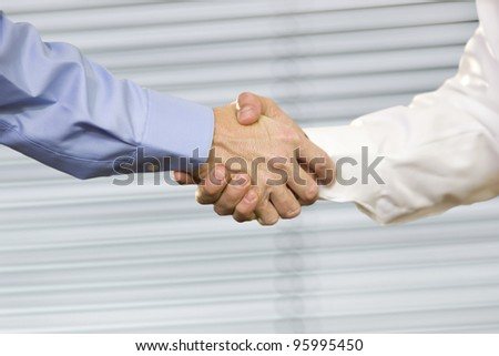 Closeup of two Caucasian men shaking hands.