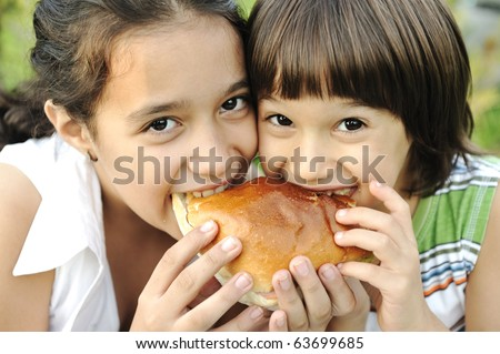 Closeup of two children eating sandwich in nature together, healthy food, care and love #63699685