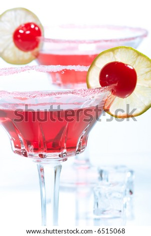 Closeup of two Cosmopolitan cocktails in martini glasses. Vodka, cranberry juice, triple sec liqueur, lime juice, garnished with lime and maraschino cherry. Most popular cocktails series. - stock photo