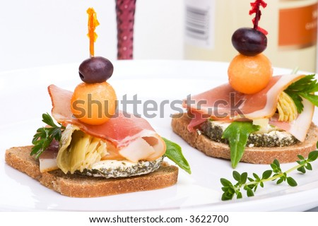 Closeup of two delicious Prosciutto canapes-sandwiches made from marinated artichoke, goat cheese,  Prosciutto ham, melon and olive over white background
