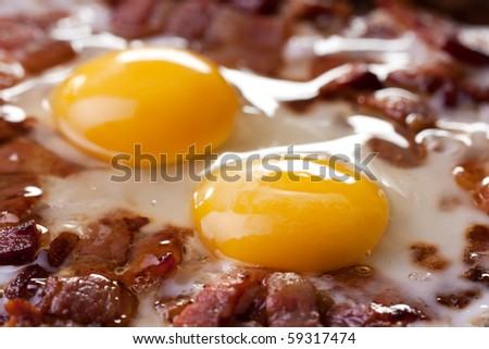 closeup of two eggs and bacon in a pan - stock photo