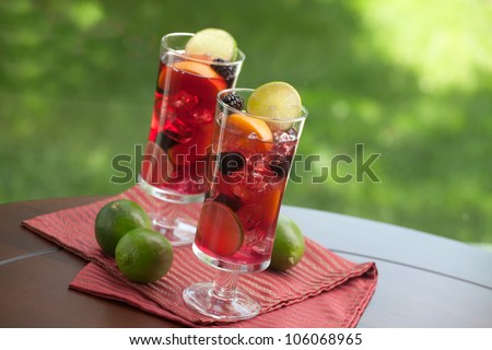 Closeup of two glass of Red Sangria - apricot, lime and blackberry - on outside table.