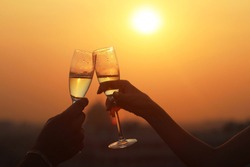 Closeup of two glasses of champagne or wine, couple dating concept, romantic celebration of engagement or anniversary on the sundown lights.