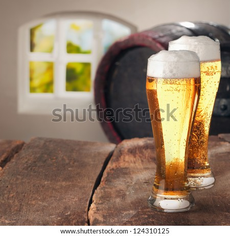 Closeup of two glasses of tasty fresh beer on a wooden table