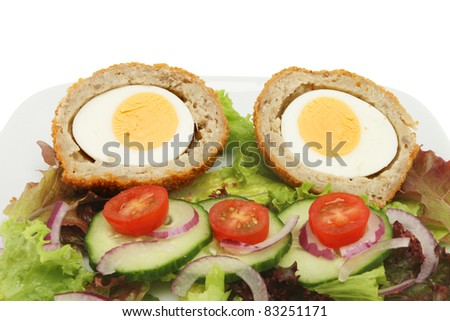 Closeup of two half scotch eggs and salad